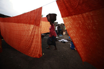 A girl walks between dyed textile hung out to dry in Air France 2, a neighbourhood in Bouake