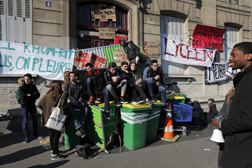 French high school students block the access to the Lycee Arago with garbage containers as they protest a labour reform bill presented by Labour Minister El Khomri, in Paris