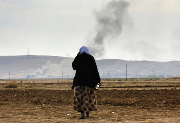 A female Kurdish refugee tries to call relatives who are still trapped in Kobani as thick smoke rises from the Syrian town during heavy fighting as seen from near the Mursitpinar border