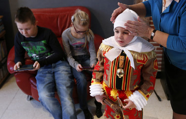 Noah Drugmand is dressed by his aunt before taking part in the parade of Young Gilles of Binche during the carnival event in Binche