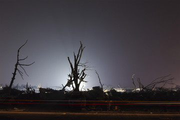 The rear lights of a police cruiser draw a line below trees illuminated by the evening light in an area heavily damaged by a tornado in Moore, Oklahoma