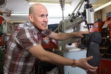 Senior workman sewing leather boots on stitch lathe