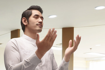 Young asian muslim man in traditional dress praying
