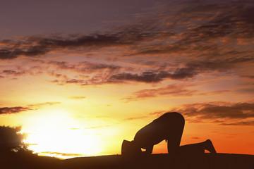 Silhouette asian muslim man with cap praying to god