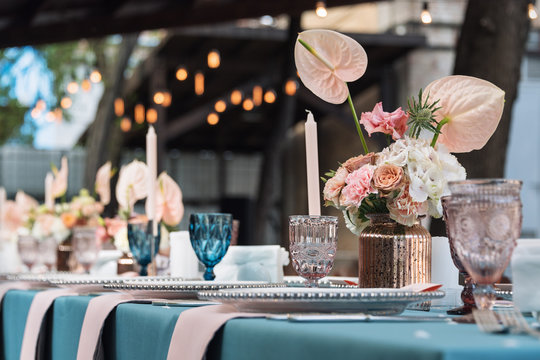 Flower table decorations for holidays and wedding dinner. Table set for holiday, event, party or wedding reception in outdoor restaurant.