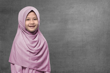 Happy asian muslim kid wearing hijab with smiley face