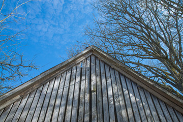 Old wooden barn facade against clear blue sky