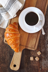 Fresh croissant and cup of coffee for breakfast. Top view