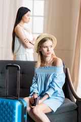 two young stylish women travelers with suitcase at room, packing luggage