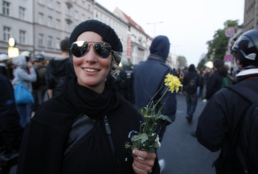 A Left-wing protestor holds a flower during May Day demonstrations in Kreuzberg district of Berlin