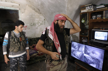 A member of the Free Syrian Army walks past camera surveillance screens in the Bab al-Nasr neighborhood of Aleppo