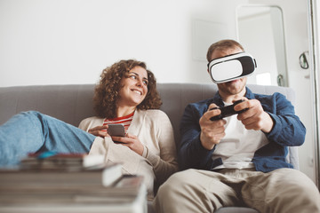 Young family spending time together with electronic devices. Man playing breathtaking computer game with VR headset. Smiling woman typing message using mobile phone