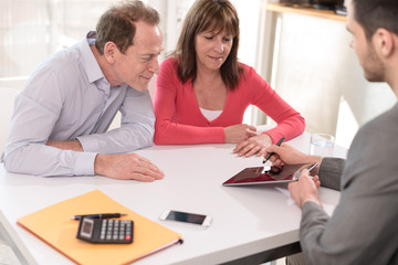 Senior couple meeting realtor for investment