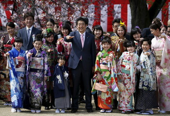 Japan's PM Abe poses with child actors, members of Japanese idol group Momoiro Clover Z and other show-business celebrities at a cherry blossom viewing party at Shinjuku Gyoen park in Tokyo