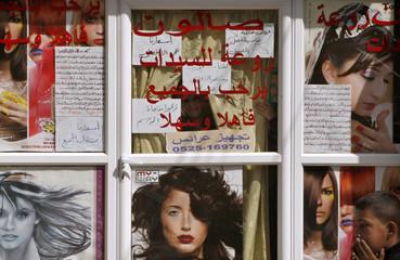 Palestinian women look through the glass door of a beauty salon as Palestinians march against house demolition orders, in the Arab East Jerusalem neighbourhood of Silwan