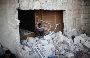 A man sits at his damaged house after an air strike by a fighter jet loyal to Syrian President Bashar al-Assad in Azaz city