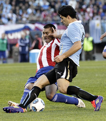 Paraguay's Da Silva and Uruguay's Suarez battle for the ball during the Copa America final soccer match in Buenos Aires