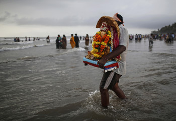 A devotee carries a statue of the Hindu god Ganesh, the deity of prosperity, to be immersed into the Arabian Sea on the fifth day of the ten-day-long Ganesh Chaturthi festival in Mumbai