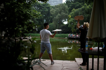 Two pizza chefs toss dough as they exercise at a park, in Shanghai, China