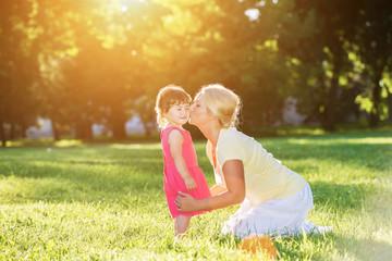 Mom kissing her little girl in the sunset park.Lens flare
