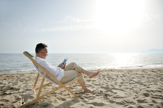 Man relaxing with tablet on the beach sitting on a deckchair