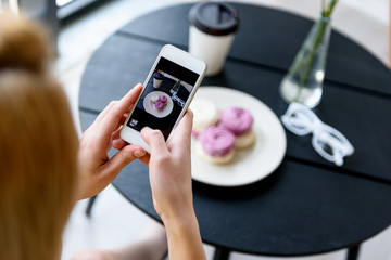 Elegant woman making shot of her dessert with coffee