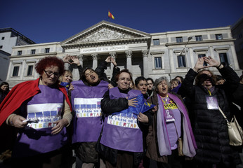 Women pose in front of the Spanish parliament after taking a petition to parliament against a government plan to limit abortions in Madrid
