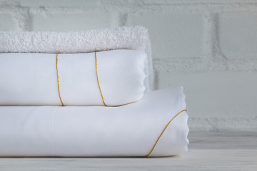 Luxury White Bed Sheets Stacked On Loft Background. Closeup.