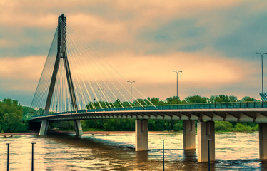 Modern bridge in Warsaw across the river next to a football stadium in the evening with a setting sun