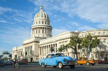 Aluminium Prints Havana Brightly colored classic American cars serving as taxis pass on the main street in front of the Capitolio building in Central Havana, Cuba