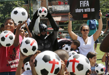 Children and an anti-government demonstrator, dressed as comic book superhero Batman, pose for picture with soccer balls during a protest at the Jacarezinho slum in Rio de Janeiro