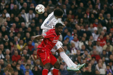 Real Madrid's Raphael Varane challenges Liverpool's Kolo Toure during their Champions League Group B soccer match at Santiago Bernabeu stadium in Madrid