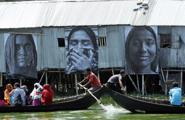 Boats carrying slum dwellers pass photographs of garment workers taken by students of the Counter Foto photography department, by the waterfront of Korail slum at Gulshan area in Dhaka