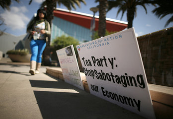 A student walks past signs at an education and awareness event on the Affordable Care Act and protest against Tea Party officials organizers say are threatening an economic shutdown, in Santa Monica