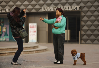 A woman takes a picture with her pet dog at a shopping mall in Beijing