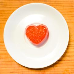 Closeup on love heart shape red caviar delicacy on white plate, closeup light macro background