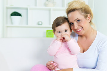 Portrait of smiling mother and  little baby girl in her arms.Copy space, shallow doff