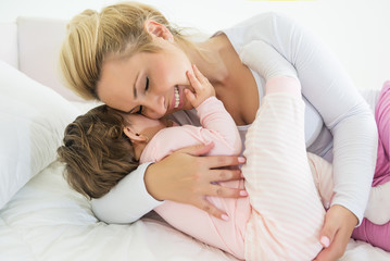 Mom and baby little girl in a gently hug in the bed.Shallow dof