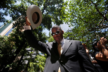 A man raises his hat in prayer during a prayer vigil in a park following the multiple police shooting in Dallas
