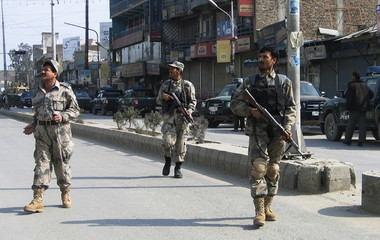 Afghan border policemen keep watch during an attack by gunmen on a bank in Jalalabad city