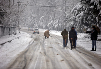 Men shovel snow to clear a road during a snowfall in Srinagar