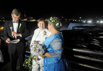 Rudd and Lambert react after being married at the stroke of midnight, at the brink of Niagara Falls, in Niagara Falls, New York