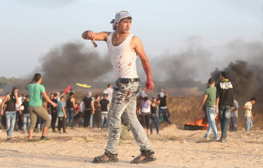 Palestinian with blood on his clothes walks during clashes with Israeli troops near the border between Israel and Central Gaza Strip