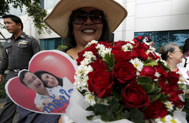 Supporter of ousted Thai Prime Minister Yingluck Shinawatra holds a picture of her and her brother, former Prime Minister Thaksin Shinawatra, and a basket of red roses at the Supreme Court in Bangkok