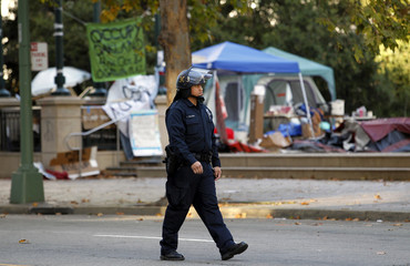 A police officer walks past a dismantled Occupy Oakland encampment at City Hall in Oakland