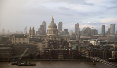 A rain cloud approaches St Paul's Cathedral in central London