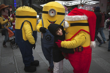 A boy hugs people dressed up as Minion characters in Times Square in the Manhattan borough of New York