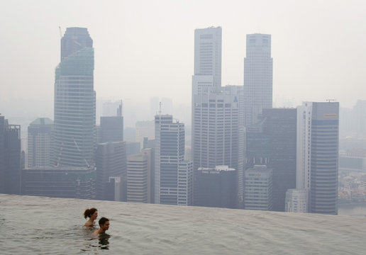Hotel guests swim in an infinity pool overlooking the haze-covered skyline in Singapore