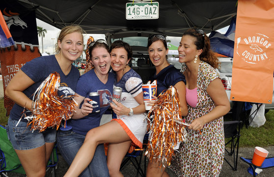Denver Broncos fans pose for pictures before the start their NFL football game against the Miami Dolphins in Miami