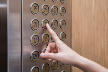 Woman's hand is pressing elevator button